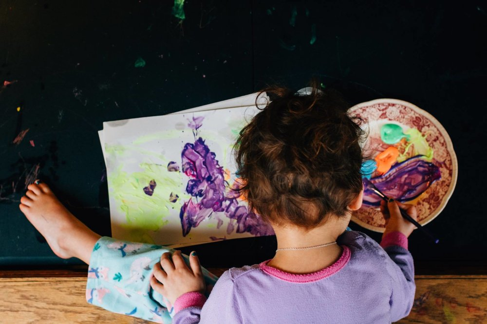A bird's eye view of a little girl painting a bright and color picture.