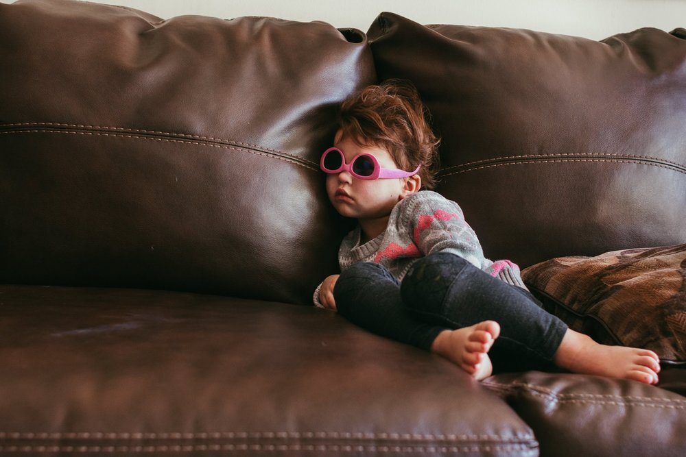 a liitle girl sitting on a couch with her sunglasses on.