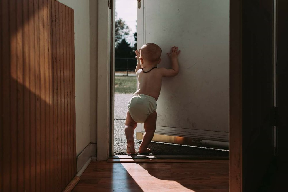 Baby boy in a yellow cloth diaper opening the door and trying to step outside. Koren Smith Photography. Family Documentary Photographer. Omaha, Nebraska.