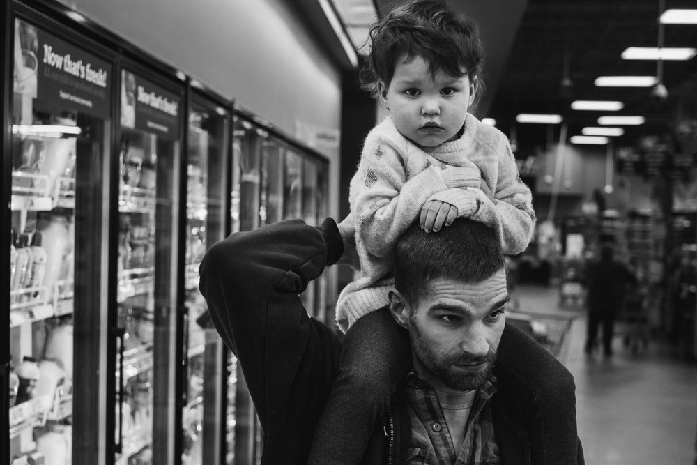 Little girl sitting on her dad's shoulders while at the grocery store