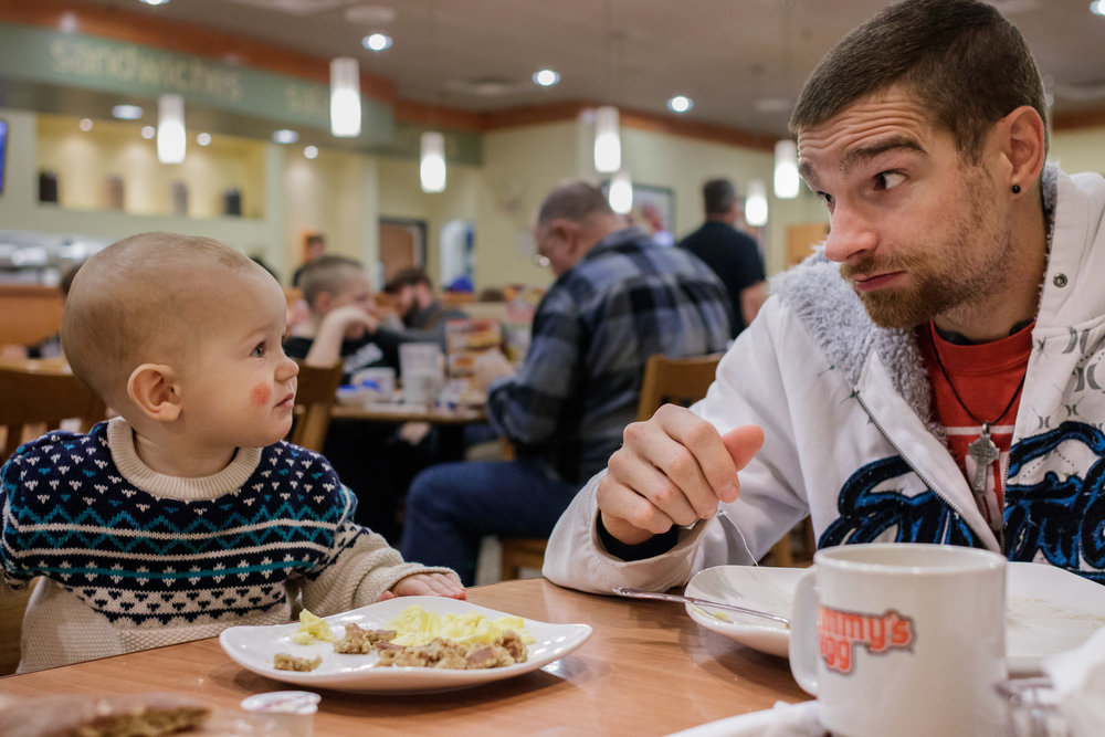 Boy and father looking at each other while eating breakfast