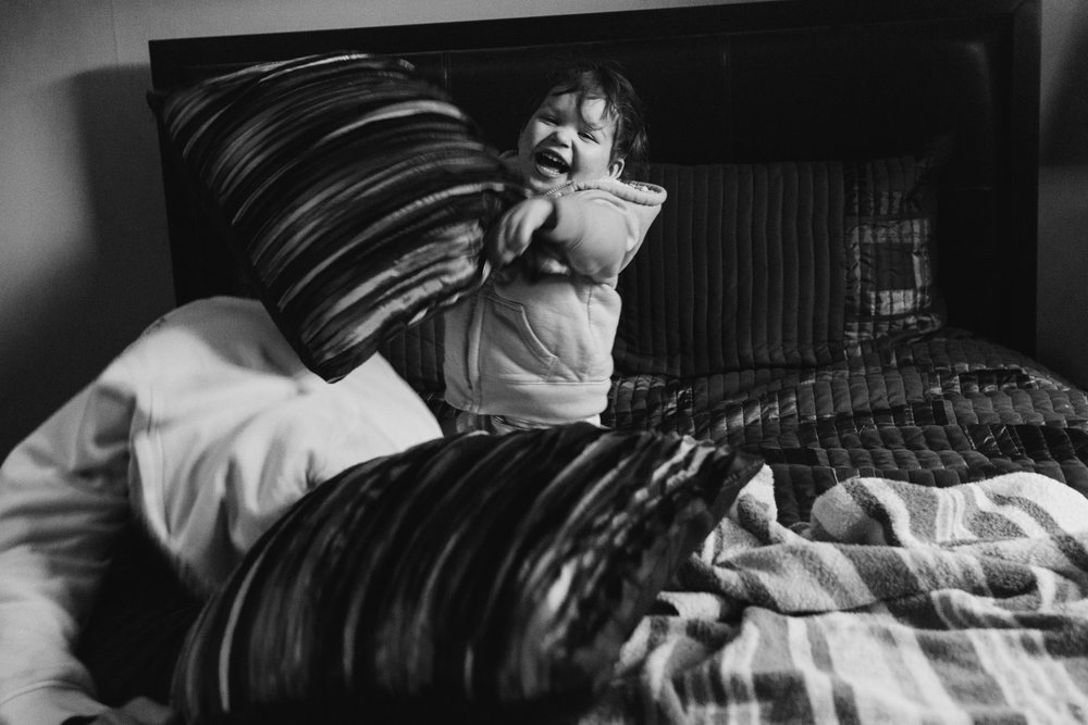 A toddler having a pillow fight with her father at her grandpa's house.