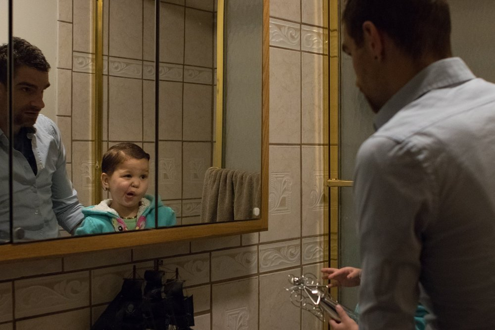 Girl making funny faces in the mirror.