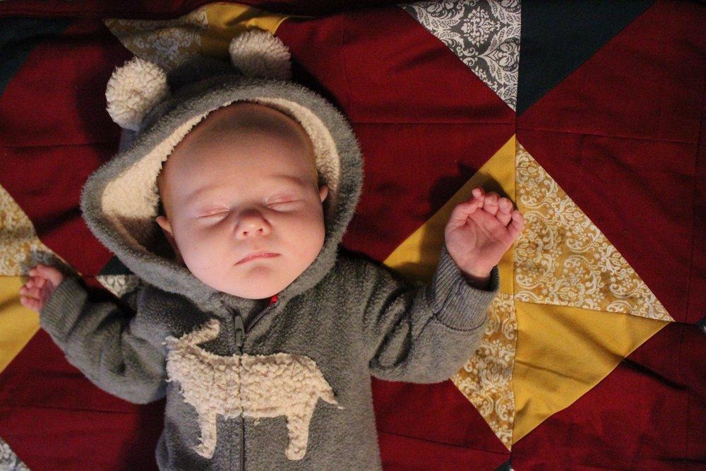 Baby sleeping on a blanket.j