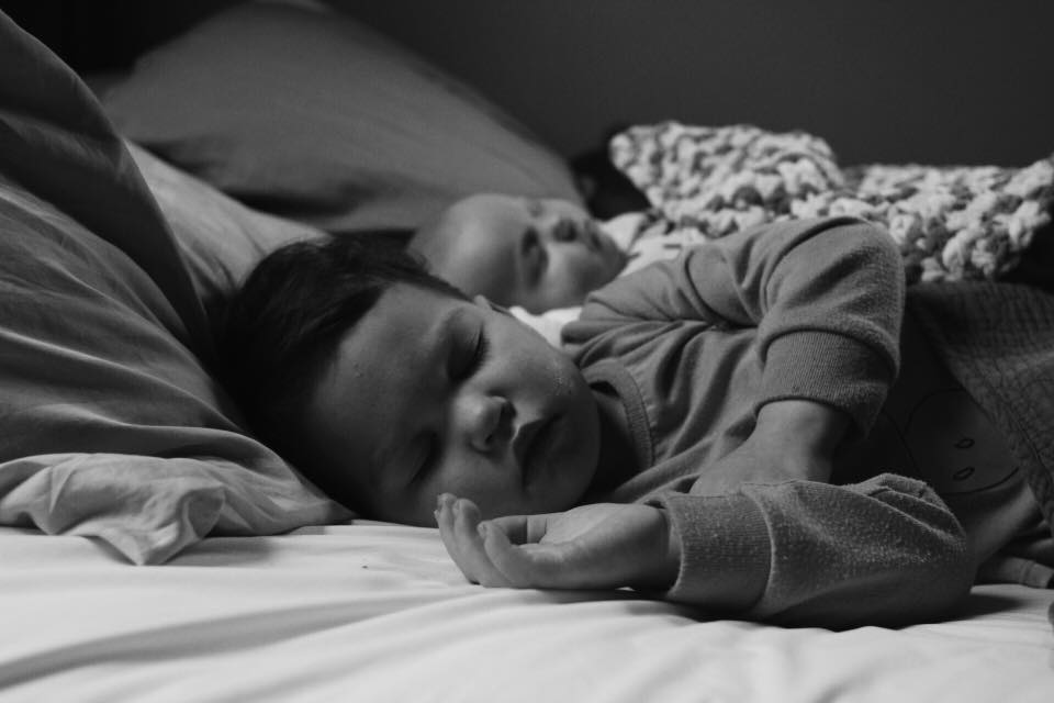 Two kids sleeping on a bed.
