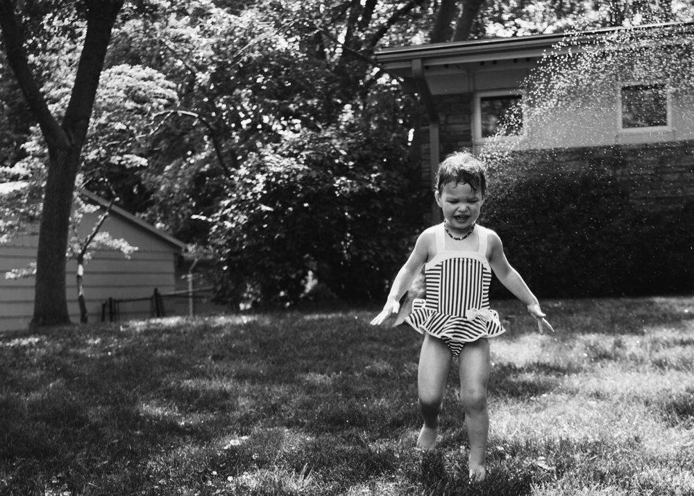Girl playing in the sprinkler.