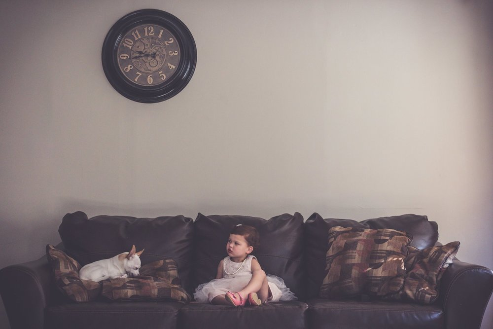 A girl and a dog sitting on the couch.