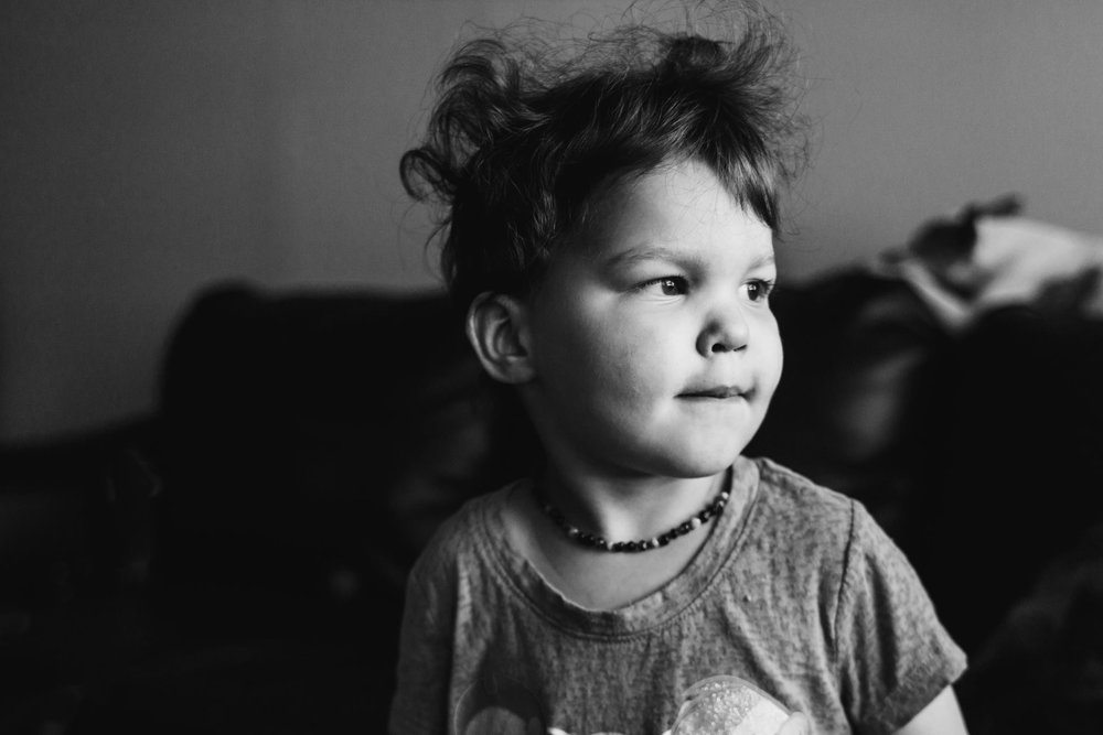 A little girl looking off camera with wild bed head.