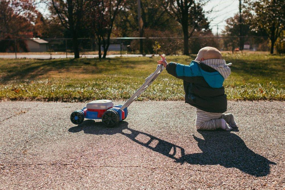boy pushing toy mower.