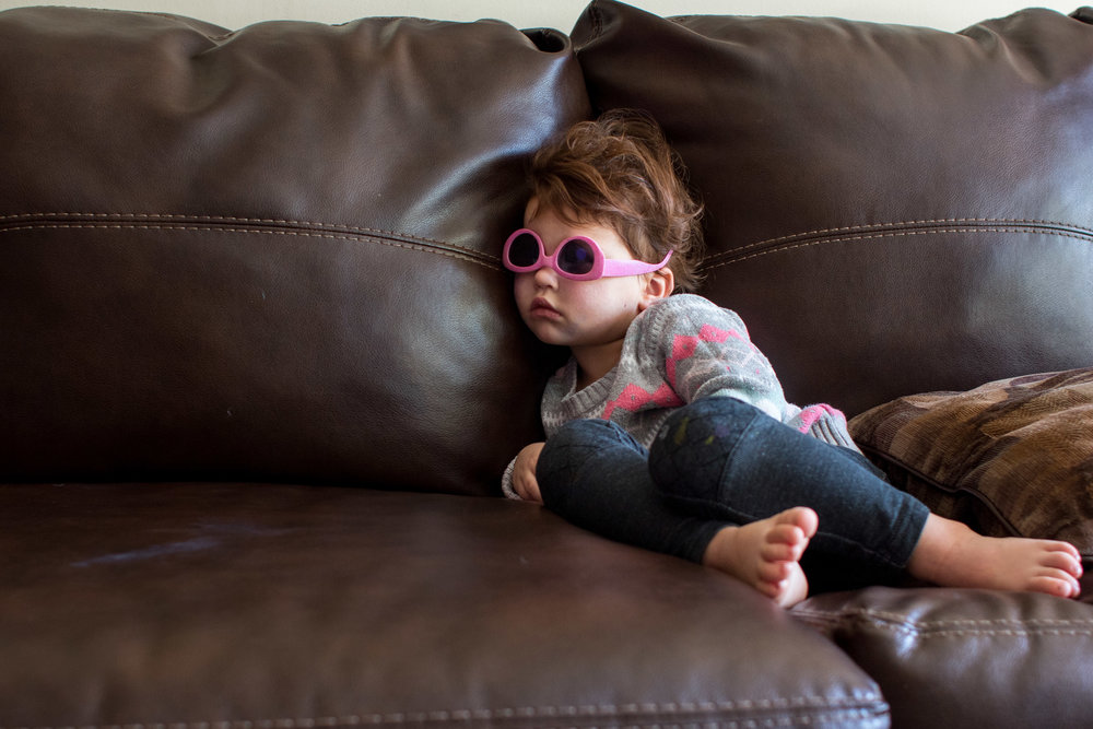 Girl on the couch with upside down sunglasses