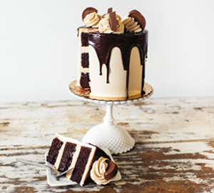 Peanut Butter Loves Chocolate - Chocolate Cake filled with Peanut Butter Frosting covered with Peanut Butter Swiss Meringue, Chocolate Drips, Frosting Rosettes & Peanut Butter Cups