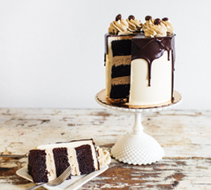 Mocha Latte - Chocolate Cake filled with Espresso Swiss Meringue covered with Vanilla Swiss Meringue topped with Ganache drips, espresso buttercream rosettes, chocolate covered espresso beans