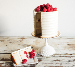 Almond White Chocolate Raspberry - Three layers of Almond Cake filled with White Chocolate Mousse and fresh raspberries, Cream Cheese Frosting and raspberry preserves covered in Almond Swiss Meringue Buttercream and topped with a pile of Raspberries