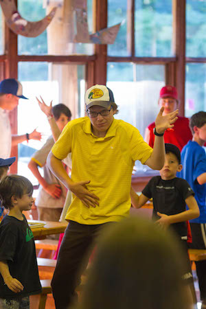 Camp counsellor does the jig of joy in a camp dining hall
