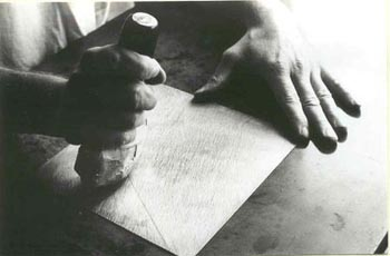 artist using a rocker tool on mezzotint plate
