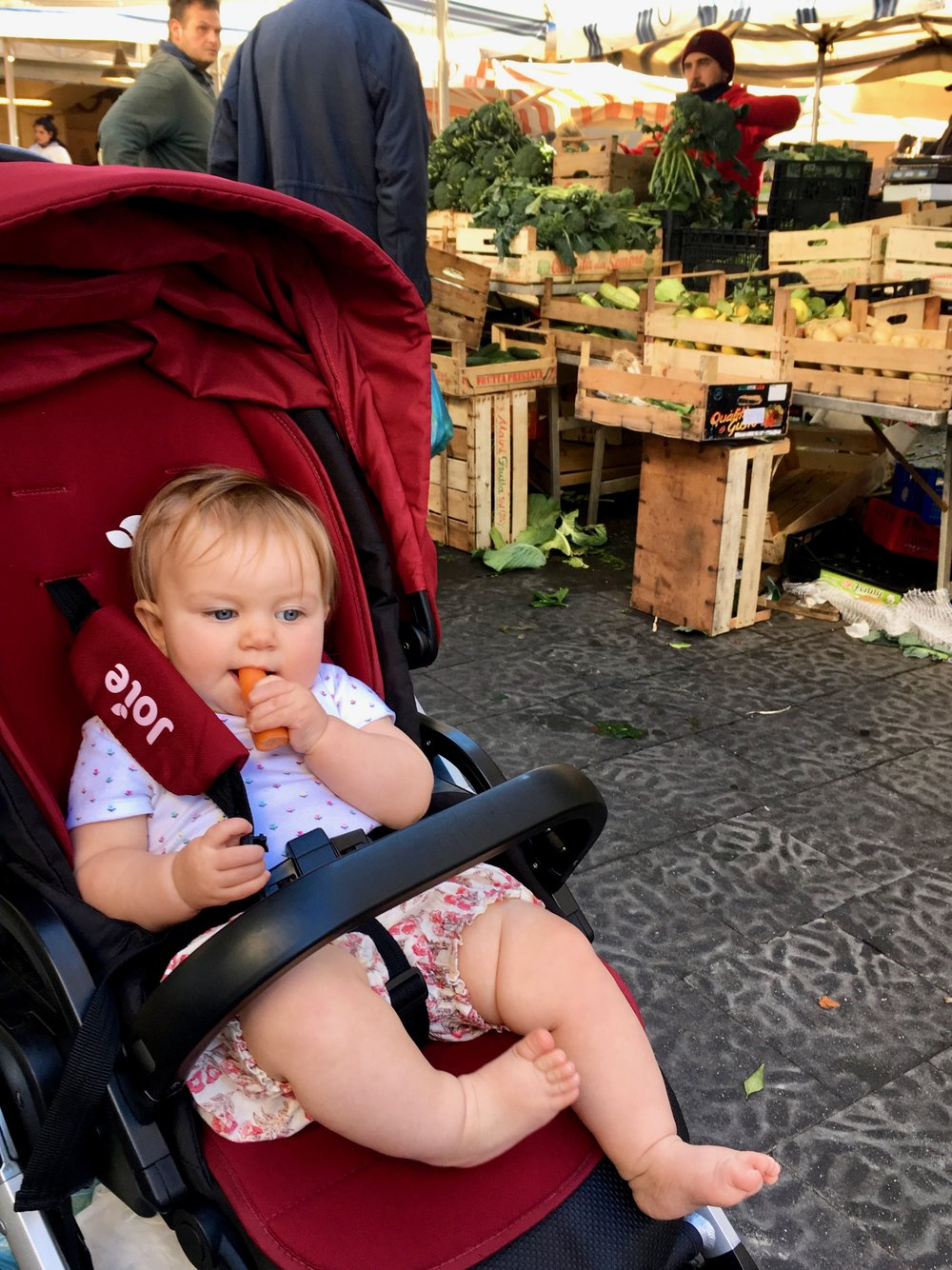 Boss Baby snackin' on a fresh carrot at the market.