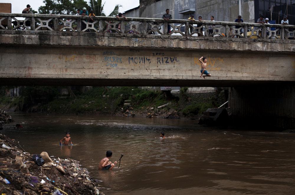 Local kids cool off in Ciliwung River in Jakarta.