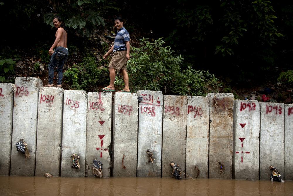 Men walk along a new floodwall in Jakarta.