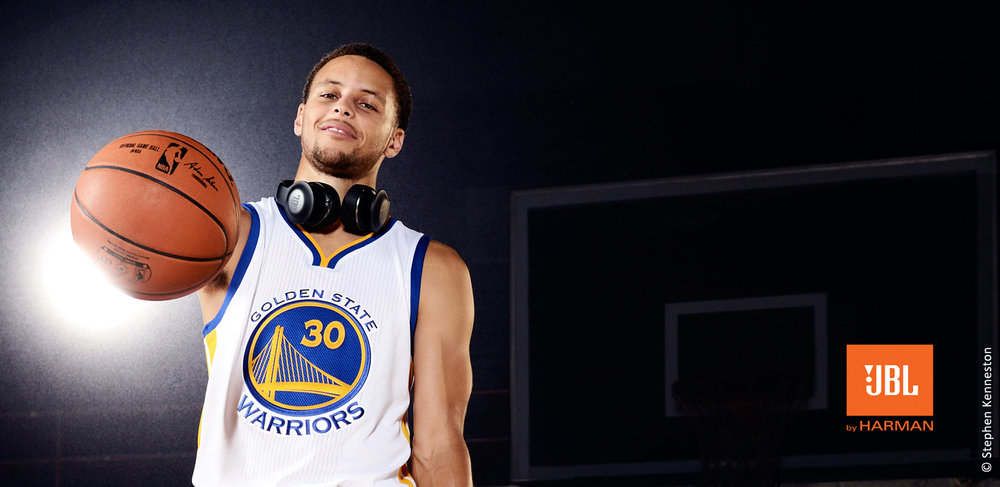 photo of Steph Curry wearing JBL headphones around his neck holding a basketball with one hand in front of a bright spot light
