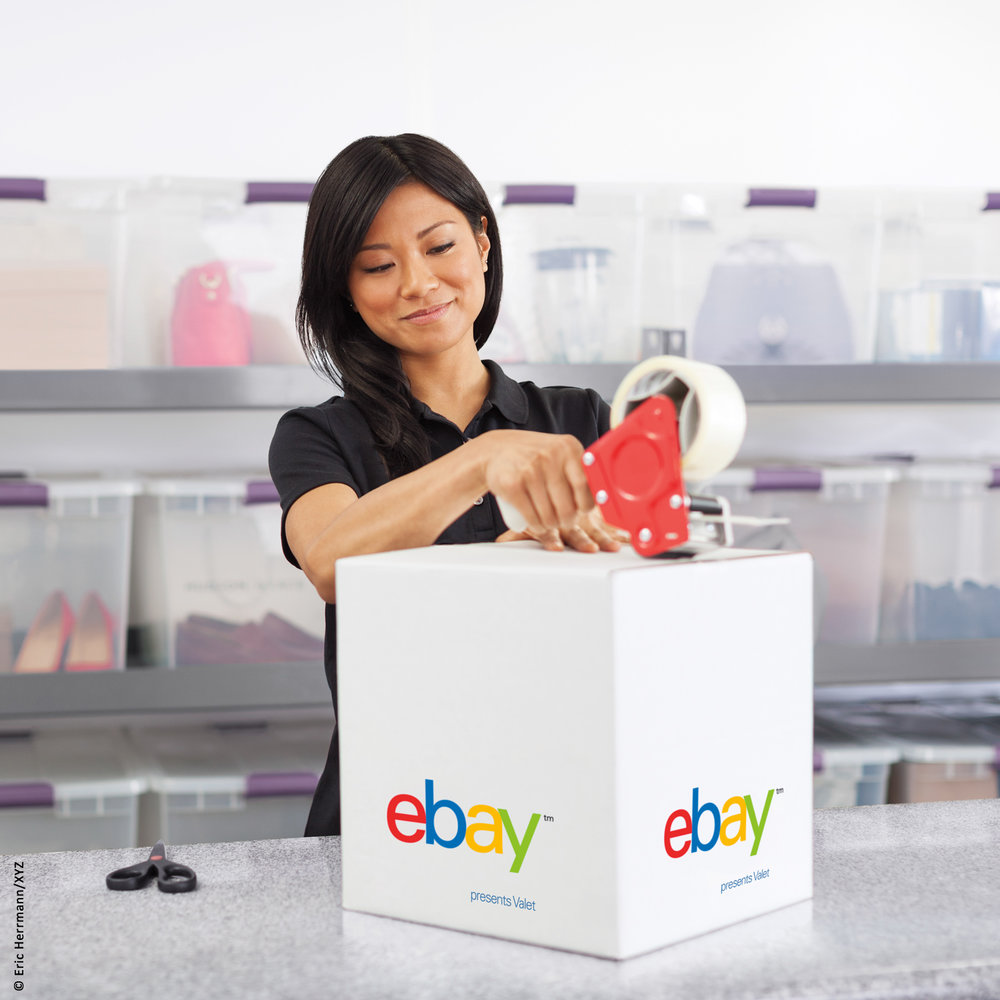 photo of smiling women behind a counter in a warehouse shipping center taping closed an eBay valet box