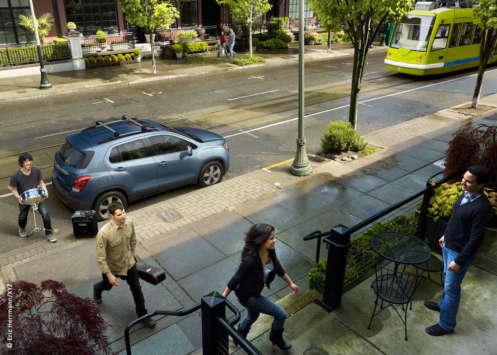 photo of street car on an urban street location with four young models carrying musical instruments from a Chevy Trax car