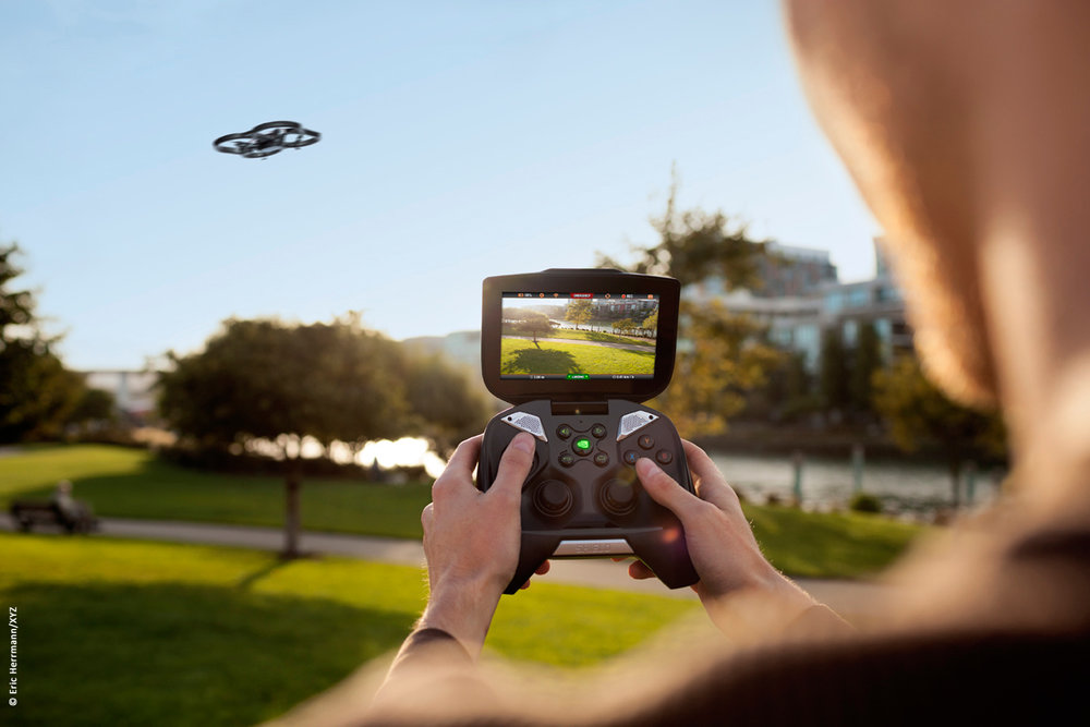 close up photo of a male model at a park location operating with his Nvidia Shield device to fly a drone