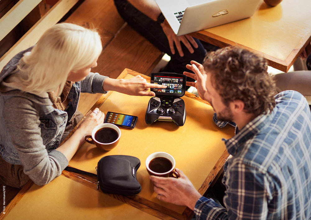 photo of a man and woman drinking coffee at a cafe viewing images streaming on the screen of a nvidia shield