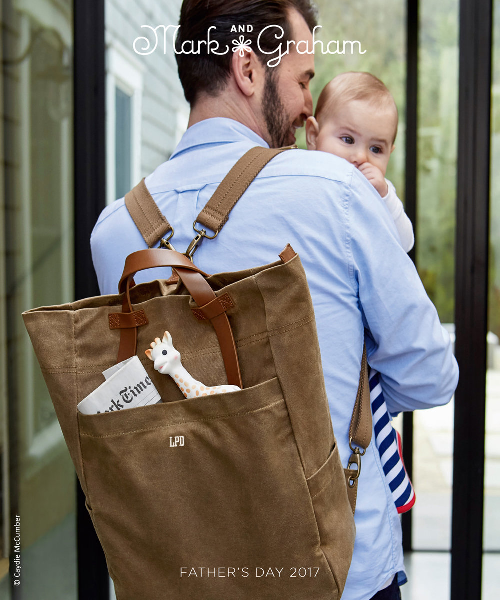 photo of Mark and Graham catalog cover of father wearing a backpack carrying his baby boy in the house