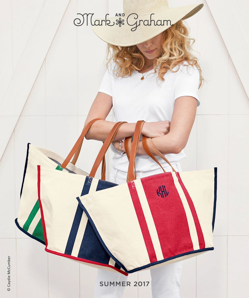 photo of a female model in wide brimmed straw hat holding three striped canvas beach totes for catalog cover