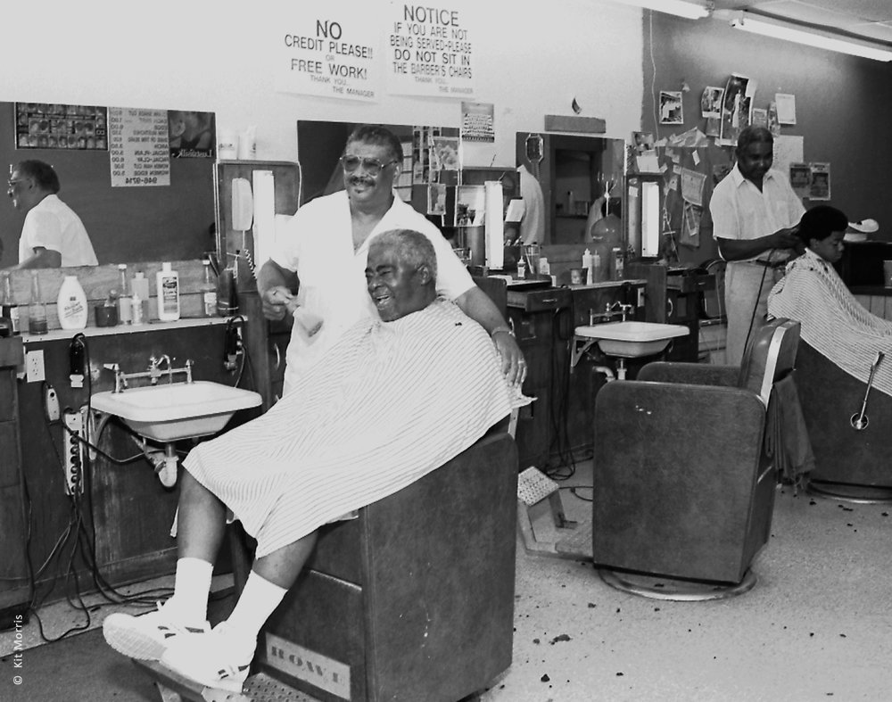 Photo of at Dallas barbershop location where smiling barber gives a haircut to kidney transplant patient before his grand daughter's wedding