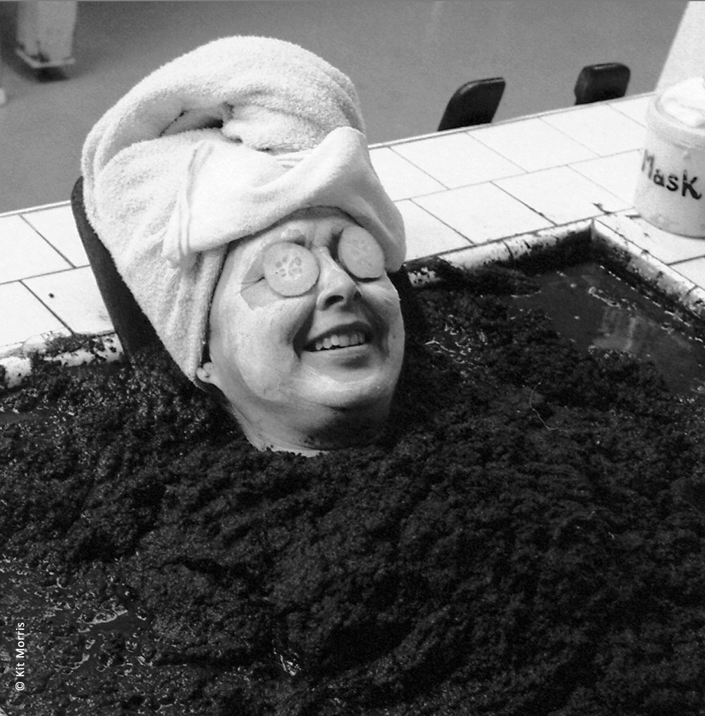 photo of women wearing a turban and cucumbers over eyes sits in a mud bath to celebrate her continued good health