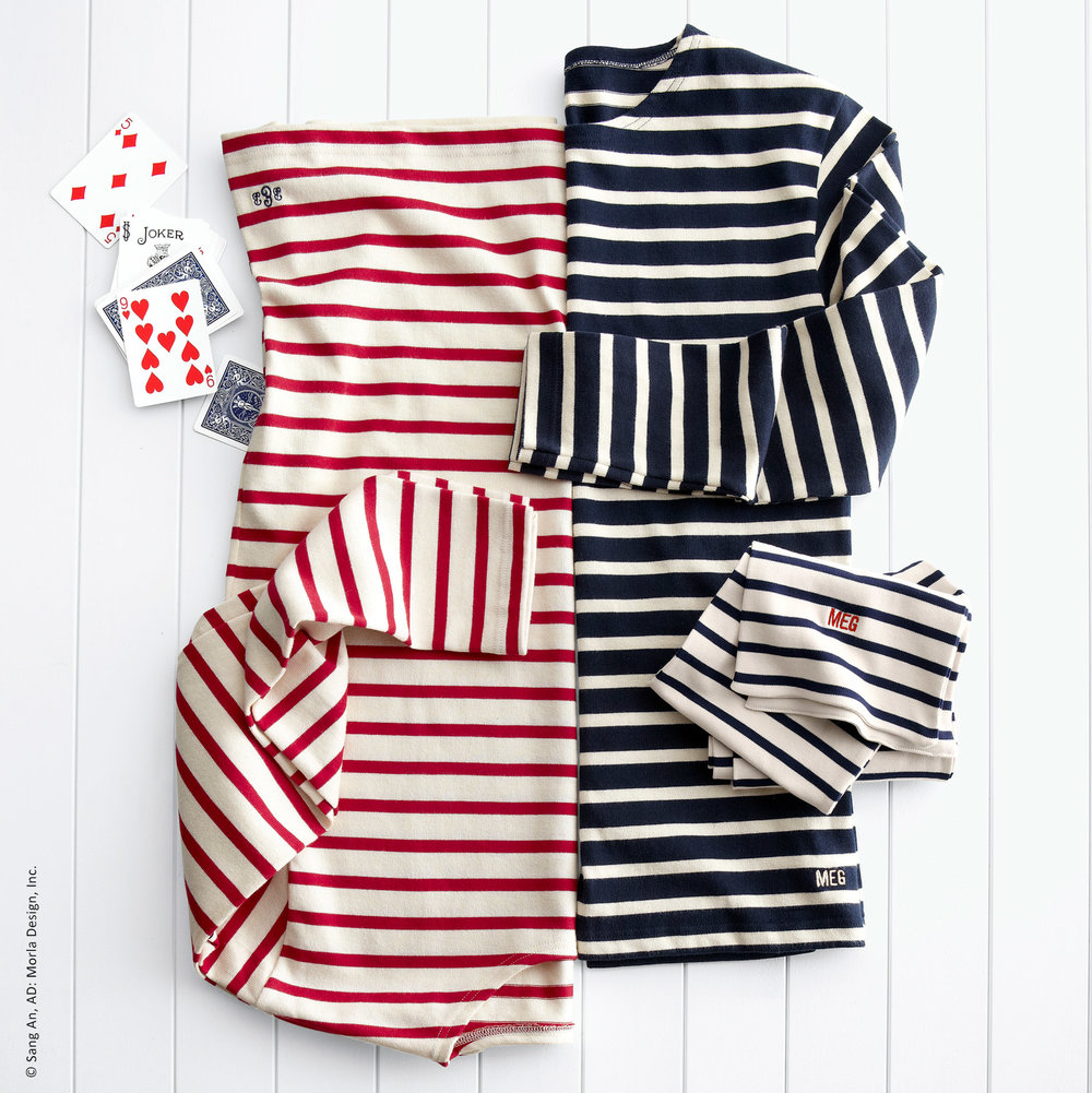 Laydown apparel photo of red, navy & white striped scarf and dresses on a wood set for Williams-Sonoma, Inc.