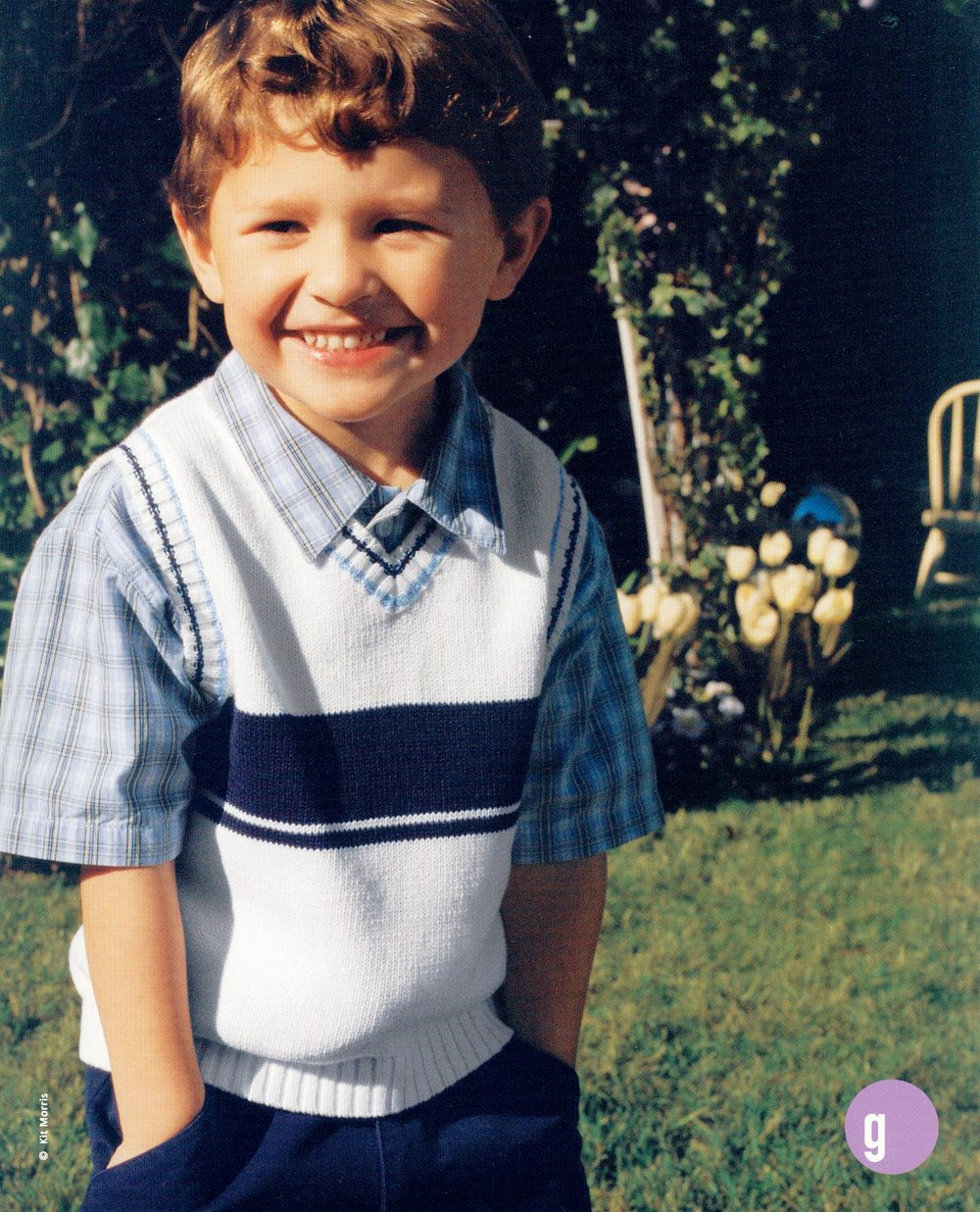 Photo of a smiling kid wearing his dress-up Easter clothes hands stuffed in his pants pockets standing in a sunny garden location