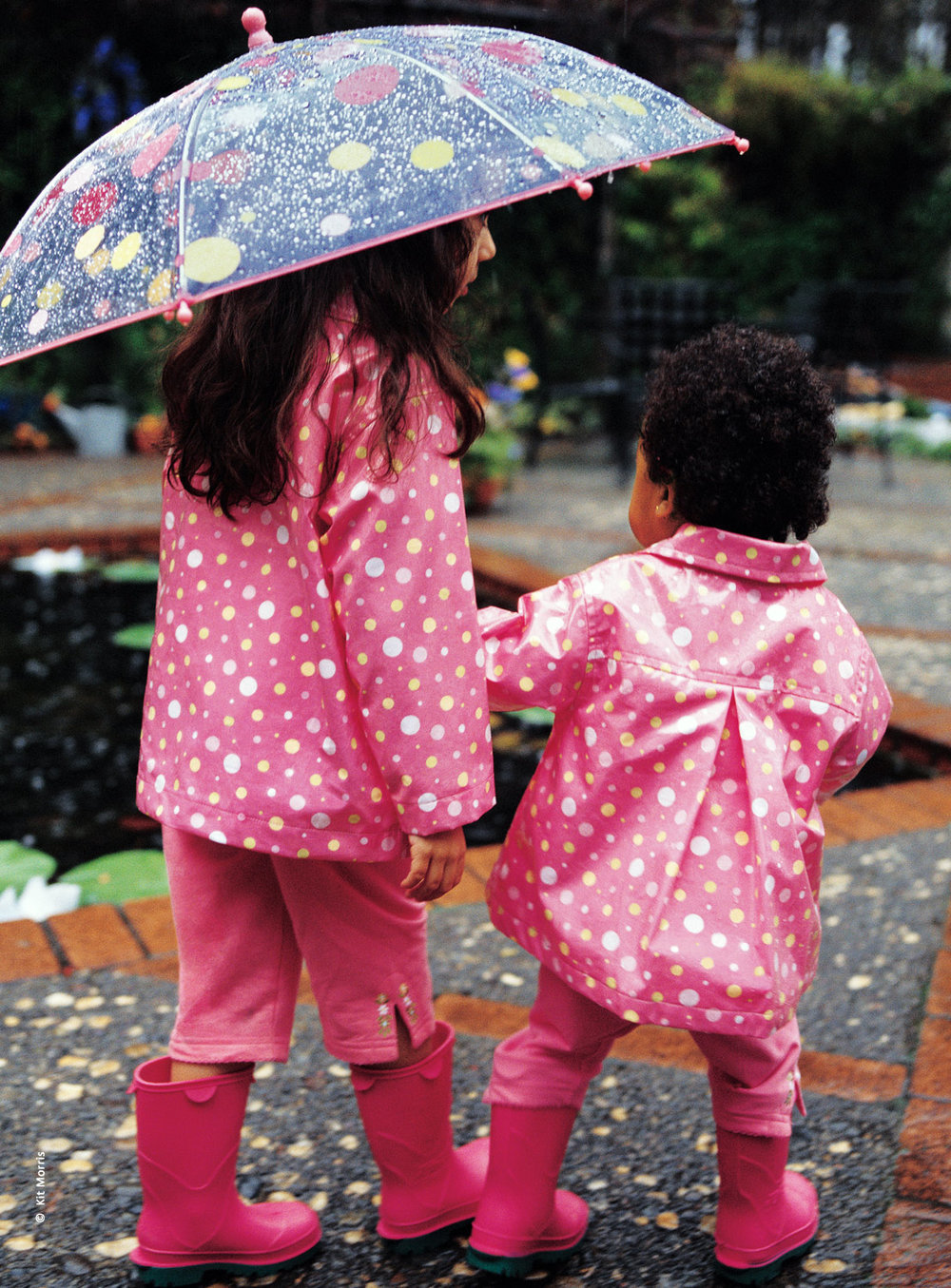Photo of two young girls walking under a umbrella by a pond wearing matching pink and polka dot outfits by children's apparel company Gymboree