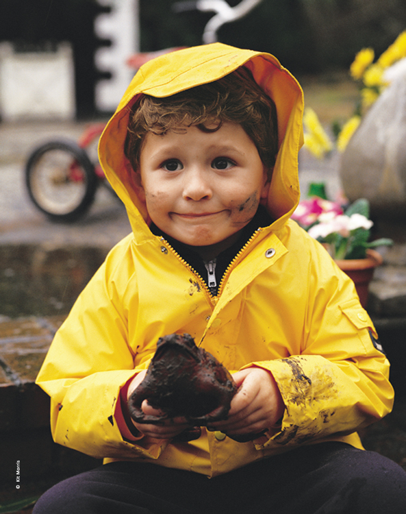 Photo of little boy with a funny smile wearing a yellow rain coat sitting on wet steps holding a muddy frog