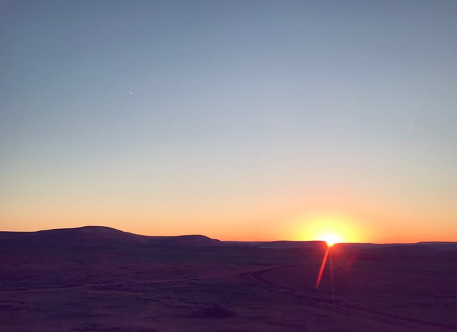 """At 6am, driving to Casablanca International airport, I asked my driver if he wouldn't mind pulling over so I could take a photo of the sunrise over the Atlas Mountains. I think he was amused and happily led me to a small road with this view. It was a crisp morning and now a beautiful memory."""