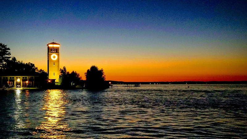 Chautauqua Bell Tower on Chautauqua Lake with beautiful blue and orange sky at sunset