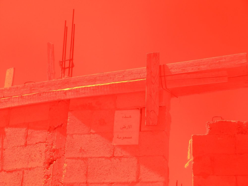 Photograph with red sheet filters corresponding to caesium 137 levels in Khirbet Al Taybeh, Hebron from Inas Halabi, Lions Remind Us of Futures Present (artist book), 2017. Courtesy of the artist.