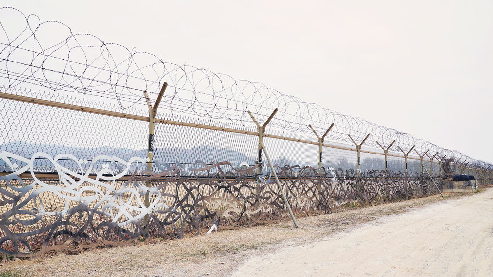 The barbed wire fence between North and South Korea represents discord and violence. eL Seed's artwork is a message of unity.