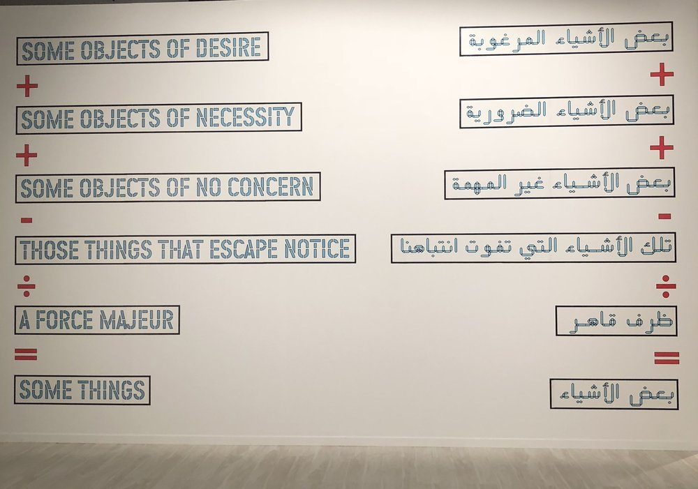 The first work that hangs in  From Barcelona to Abu Dhabi - Works from MACBA in dialogue with the Emirates.  Lawrence Weiner's text-based piece  Some Objects of Desire  that has been translated for this exhibition from English to Arabic. Image taken by Anna Seaman
