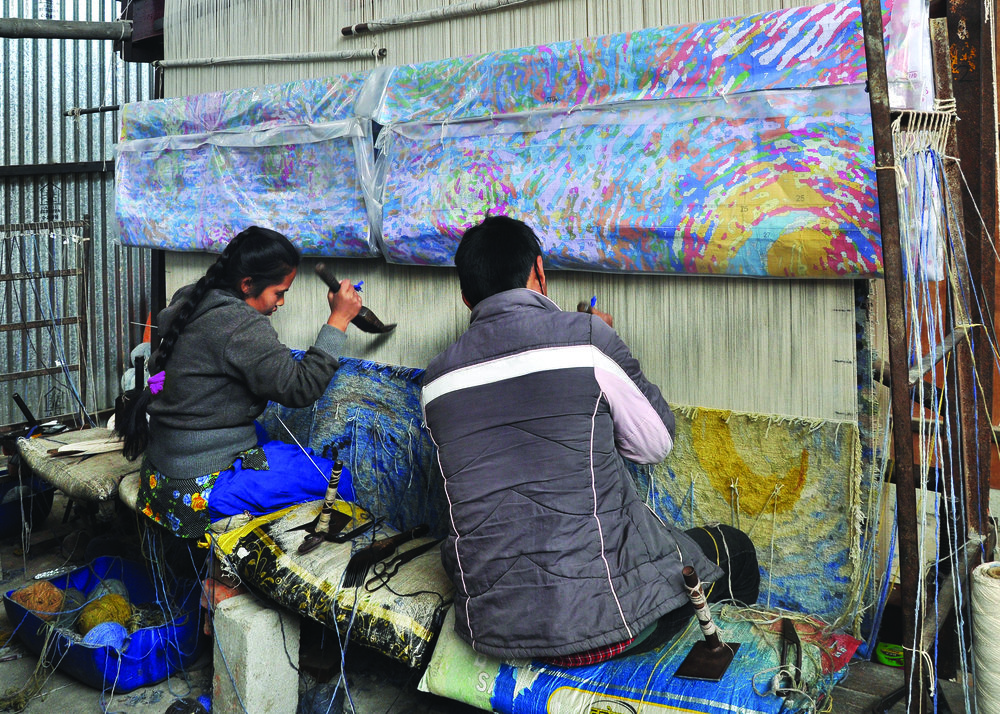 Workers in the process of weaving the 150 knot per inch carpet that translates Van Gogh's masterpiece The Starry Night into a fabric artwork. Image courtesy of Samovar Carpets