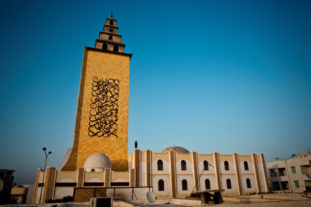 eL Seed's Jara Mosque project in his home town of Gabes, Tunisia. On the side of the minaret he wrote the words of a Quranic verse, which shows the true uniting spirit of Islam. Courtesy eL Seed Studio.