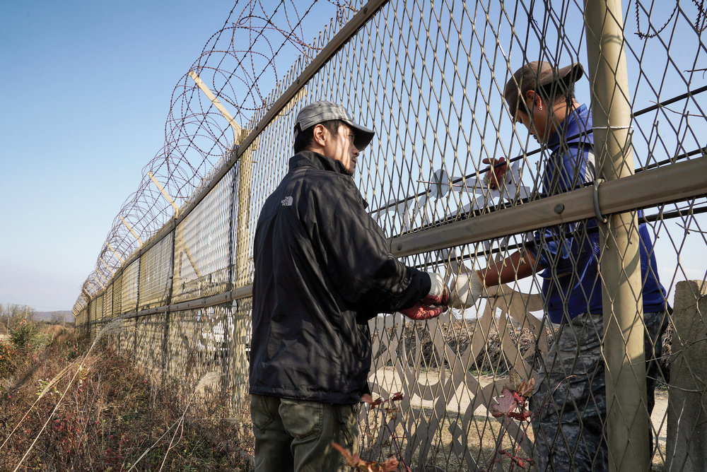 Crossing boundaries and creating ties is eL Seed's intention as an artist and as a human. Here two people work together on either side of the fence in the DMZ, symbolising the unity that his artwork brings. Courtesy eL Seed Studio.