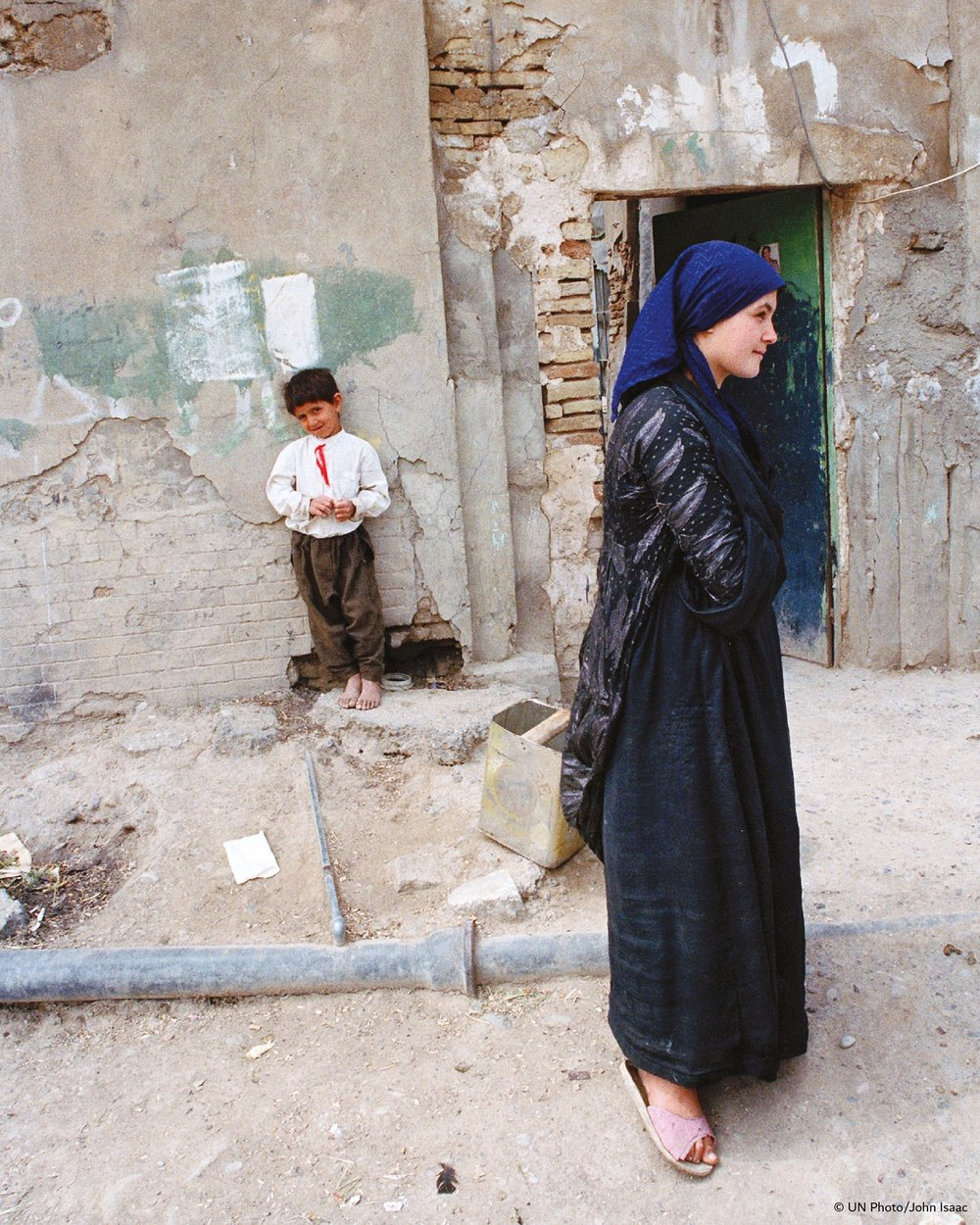 A Kurdish family stand outside a damaged home in Erbil, northern Iraq in 1991. Courtesy UN Photo/John Isaac.