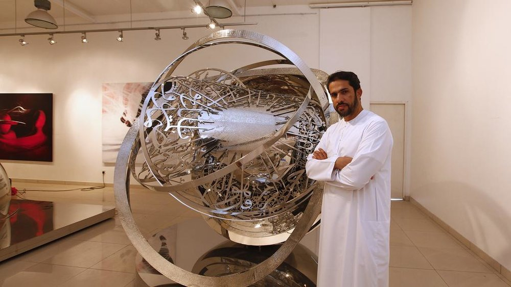 Mattar Bin Lahej stands next to one of his large sculptures made from calligraphic lettering and summarising his artistic practice focused on movement. Image courtesy of The National