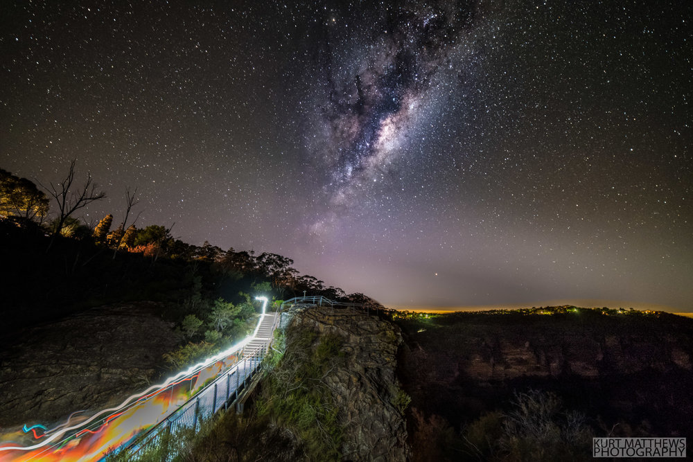 Runners pass over a cliff top bridge below the milky way.