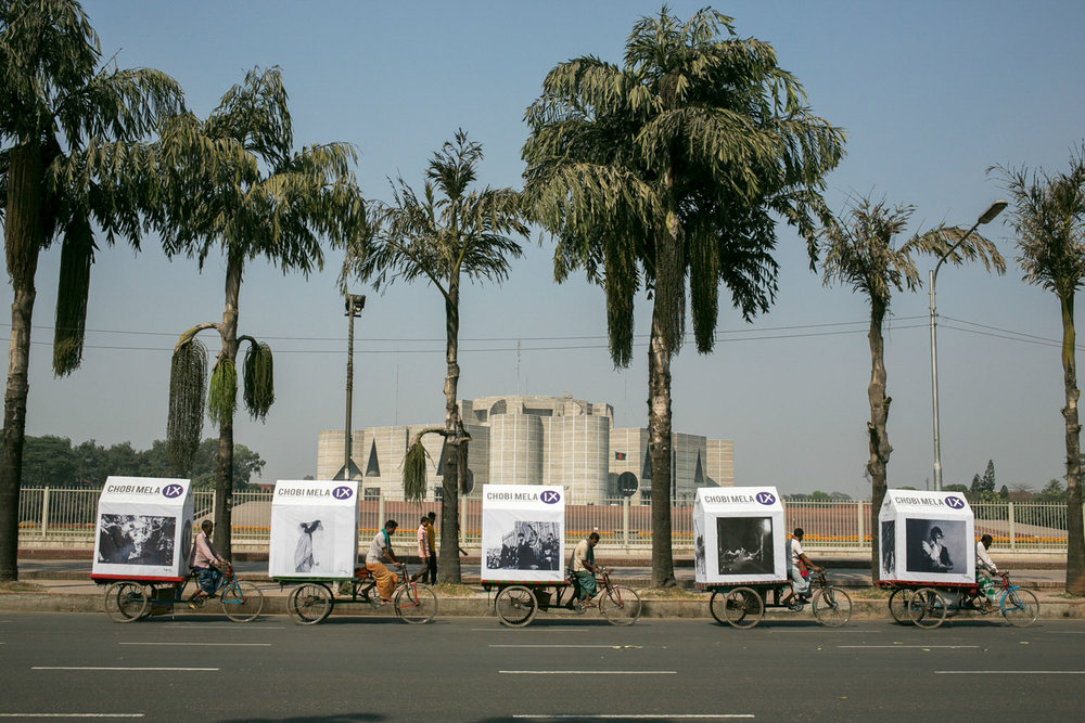 Chobi Mela's mobile exhibition, cycling on rickshaws past Parliament House