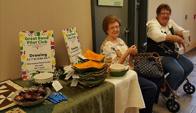At the Summit Marilyn Kopke and Marcia Johnson sell changes on 2 table runners made by Lynette Blakeslee and Billie Bonomo and sell Microwave bowl cozies (cut out by Pilot members & sewed by Billie Bonomo.