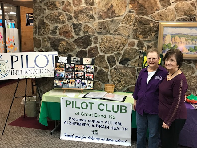 Membership cochairs Joyce Fry and Mary Lou Stewart pose with their display at the Great Bend Pilot Library depicting Great Bend Pilot Club banners and pictures of past events.