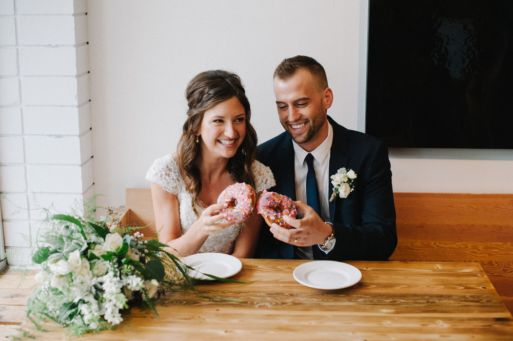 Vancouver Wedding Photographer - Bride And Groom Eating Donuts At A Coffee Shop